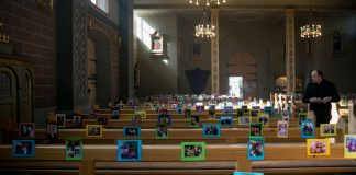 Priest walks by pews with photos of congregation attached to them.